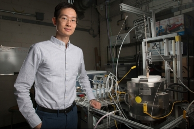 XiaoYu Wu, with the reactor his team used for the research