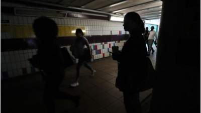People walk in the darkness in the London tube